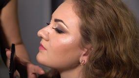 Piękno bar Młody piękny dziewczyna model siedzi w krześle Makeup artysta robi dziewczyny makeup Blondynka w pięknie zbiory wideo