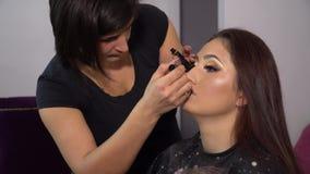 Piękno bar Młody piękny dziewczyna model siedzi w krześle Makeup artysta robi dziewczyny makeup Brunetka w pięknie zbiory