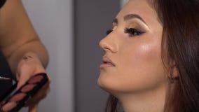 Piękno bar Młody piękny dziewczyna model siedzi w krześle Makeup artysta robi dziewczyny makeup Brunetka w pięknie zdjęcie wideo