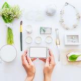 Piękno blogu pojęcie Zakończenie w górę żeńskich ręk utrzymuje smartphone na tle projektujący greenery biali akcesoria i datails zdjęcie stock