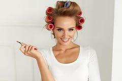 piękno Dziewczyna Fryzuje włosy Z Włosianymi Curlers, Stawia wargi glosę fotografia stock