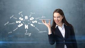 Piękno dziewczyna trzyma niewidzialną tacę z copyspace stoi blisko ściany z biznesowym pomysłu nakreśleniem rysującym na nim w ko Zdjęcia Stock