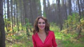 Piękno dziewczyna w czerwieni sukni z Zdrowy Długie Włosy w lasowym portrecie Szczęśliwa kobieta w jesieni w zwolnionym tempie, o zdjęcie wideo