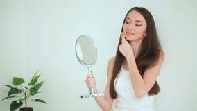 Piękno i opieka Kobieta Stosuje śmietankę Na skórze Piękna młoda kobieta z czystą świeżą skórą dotyka jej twarz facial zdjęcie wideo