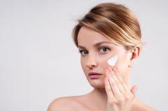 Piękno i skincare pojęcie Młoda kobieta stosuje moisturizer na twarzy Zdjęcie Stock