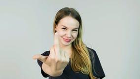 Piękno kobieta pokazuje środkowego palec i ono uśmiecha się na białym tle Obraz Royalty Free