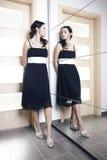 Piękno kobieta pozuje w czerni sukni za mirrow zdjęcia stock