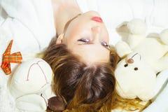 Piękno kobieta z makeup i długie włosy relaksujemy w łóżku z zabawkami Piękno kobieta z piękna spojrzeniem z miękkimi zabawkami Zdjęcia Stock