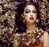 Piękno kobieta z twarzy sztuką i biżuteria od kwiat orchidei up, kreatywnie makeup kwiecistego deseniowego tła zamkniętego, Zdjęcia Stock