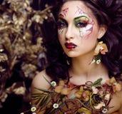 Piękno kobieta z twarzy sztuką i biżuteria od kwiat orchidei up, kreatywnie makeup kwiecistego deseniowego tła zamkniętego, Obraz Stock