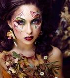 Piękno kobieta z twarzy sztuką i biżuteria od kwiat orchidei up, kreatywnie makeup kwiecistego deseniowego tła zamkniętego, Fotografia Stock