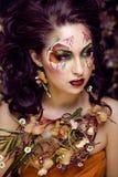 Piękno kobieta z twarzy sztuką i biżuteria od kwiat orchidei up, kreatywnie makeup kwiecistego deseniowego tła zamkniętego, Fotografia Royalty Free