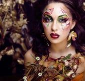 Piękno kobieta z twarzy sztuką i biżuteria od kwiat orchidei up, kreatywnie makeup kwiecistego deseniowego tła zamkniętego, Obrazy Royalty Free