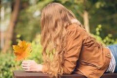 Piękno kobiety mienia jesieni liście i relaksować ławkę Fotografia Royalty Free