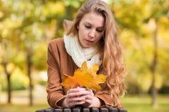 Piękno kobiety mienia jesieni liście i relaksować ławkę Fotografia Stock