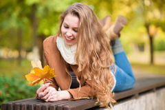 Piękno kobiety mienia jesieni liście i relaksować ławkę Obraz Stock