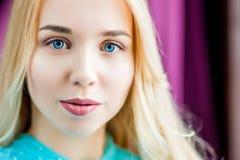 Piękno kobiety twarzy portret Wzorcowa dziewczyna jest ubranym błękit suknię pozuje w naturalnego światła pracownianym purpurowym Fotografia Stock