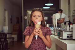 Piękno mała dziewczynka w modnej smokingowej łasowanie truskawce, stoi w lody bawialni obrazy royalty free
