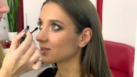 piękno nailfile paznokcie poleruje zwolnienia Młody piękny dziewczyna modela obsiadanie w krześle Makeup artysta robi makeup dzie zbiory