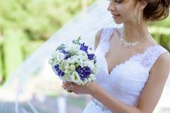 Piękno panna młoda w bridal todze z bukietem i koronkowa przesłona w naturze obraz royalty free