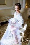 Piękno panna młoda w opatrunkowej todze z bukietem indoors Obrazy Royalty Free