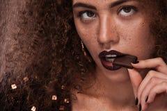 Piękno portret młoda amerykanin afrykańskiego pochodzenia dziewczyna z afro czekoladą i fryzurą Dziewczyna pozuje na brown tle Fotografia Stock