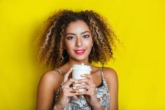 Piękno portret młoda amerykanin afrykańskiego pochodzenia dziewczyna z afro fryzurą Dziewczyna pozuje na żółtym tle, patrzeje kam Zdjęcia Stock