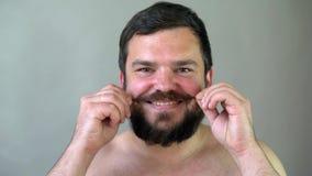 Piękno, przygotowywać i ludzie pojęć, - młody człowiek patrzeje odzwierciedlać i goli brodę z przy drobiażdżarką lub elektryczną  zdjęcie wideo