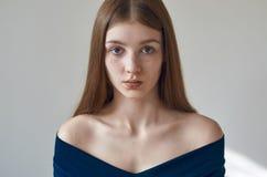 Piękno temat: portret piękna młoda dziewczyna z piegami na ona twarz i być ubranym błękitną suknię na białym tle w studi Zdjęcie Royalty Free