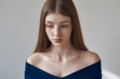 Piękno temat: portret piękna młoda dziewczyna z piegami na ona twarz i być ubranym błękitną suknię na białym tle w studi Zdjęcia Stock
