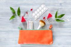 Piękno torba z kosmetykami, antykoncepcyjny i pigułkami na drewnianym stołowym tło odgórnego widoku copyspace, Fotografia Stock