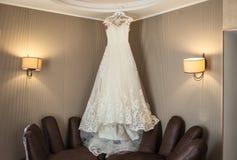 Piękny ślubnej sukni obwieszenie w pokoju, kobieta dostaje gotowy obraz royalty free