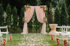 Piękny ślubny archway Łuk dekorujący z brzoskwiniowym płótnem i kwiatami zdjęcie stock