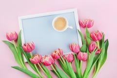 Piękny śniadanie z filiżanką kawy, wiosna tulipanu kwiatami i rama rankiem na różowym pastelowym stołowym odgórnym widoku w miesz Fotografia Royalty Free