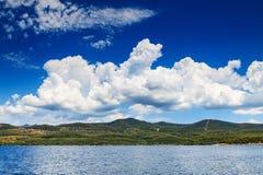 Piękny śródziemnomorski krajobraz z zieloną wyspą i chmurami Obrazy Stock