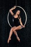 Piękny żeński akrobata obsiadanie w powietrznym obręczu pod deszczem na czarnym tle fotografia royalty free