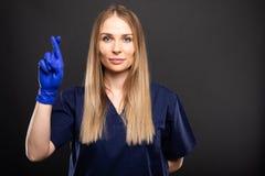 Piękny żeński dentysta jest ubranym pętaczki pokazuje palce krzyżujących fotografia stock