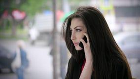 Piękny Żeński kierownika biznes dzwoni na telefonie przy miejscem pracy przeciw nadokiennej przegapia miasto ulicie zbiory
