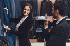 Piękny żeński menswear sklepu konsultant pomaga wybierać kurtkę dla młodego człowieka w kostiumu fotografia stock