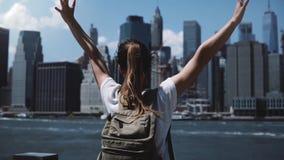 Piękny żeński podróżnik z plecak podwyżek rękami szeroko otwarty z podnieceniem blisko Manhattan miasta linii horyzontu w Nowy Jo zbiory wideo