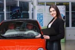 Piękny żeński sprzedawca pokazuje samochód zdjęcia royalty free