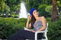 Piękny żeński uczeń czyta książkę outdoors. Obrazy Royalty Free
