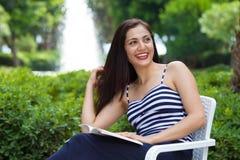 Piękny żeński uczeń czyta książkę outdoors. Zdjęcia Royalty Free
