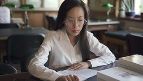 Piękny żeński uczeń pisze siedzieć indoors przy stołem w bibliotece zdjęcie wideo