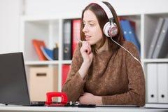 Piękny żeński uczeń słucha muzyka i uczyć się z hełmofonami Trzyma rękojeść w jego ręce i patrzeć laptopu monito zdjęcia royalty free