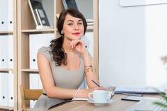 Piękny żeński urzędnika obsiadanie na miejscu pracy, ono uśmiecha się, pisać puszek informaci przy jej organizatorem, pije kawę Obrazy Stock