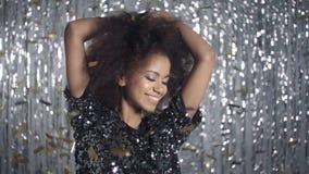 Piękny afro amerykański kobieta taniec wśród złotych confetti, zwolnione tempo zbiory