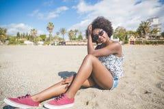 Piękny afro amerykański kobiety obsiadanie na plaży Zdjęcie Royalty Free
