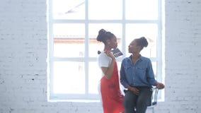 Piękny afrykanina model szczęśliwie opowiada z jej makijażu artystą podczas gdy dostawać przygotowywający dla filmować Biały stud zdjęcie wideo