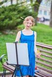 Piękny artysta na ulicie w błękitnej sukni, remisy na sztaludze Zdjęcie Royalty Free